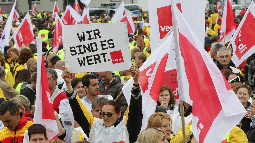 """Demonstrationsteilnehmer mit dem Schild """"wir sind es wert"""""""